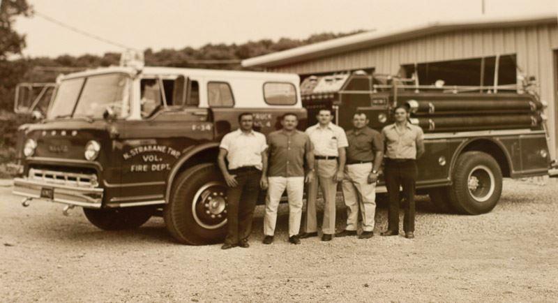 Older Black and White Photo of the Fire Department Crew with Their Fire Truck
